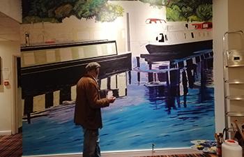 John McDonald painting this narrowboat mural in Shardlow Marina