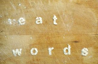 Picture of the words Eat Words made in flour on a wooden board