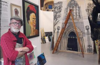 Artist John McDonald standing in front of his artwork exhibition